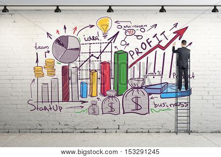 Back view of young businessman on ladder drawing creative business sketch on brick wall. 3D Rendering