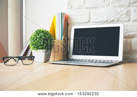 Close up of wooden desktop with blank laptop computer glasses book decorative plant and notepads. Education concept. Mock up