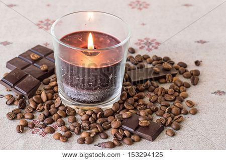 Aromatic decorative candle in a glass, coffee beans and chocolate on a linen tablecloth.
