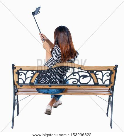 Back view woman to make a selfie stick portrait sitting on the bench. girl watching. Rear view people collection. backside view of person. Isolated over white background. girl sitting and photographed