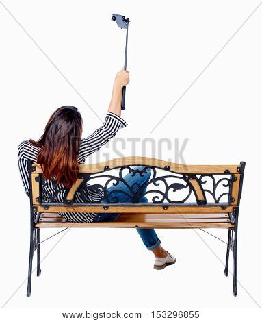 Back view of a woman to make a selfie stick portrait sitting on the bench. girl watching backside view of person. Isolated over white background. Girl on a bench in the park is photographed.