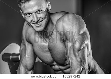 Handsome Muscular Bodybuilder Man Doing Exercises In Gym