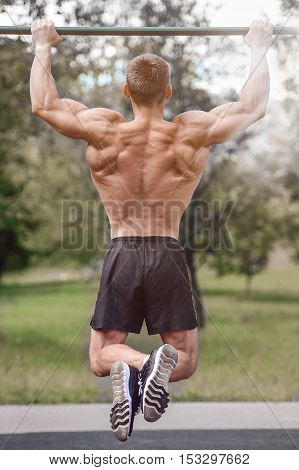 Muscular Man Practice Street Workout In An Outdoor Gym