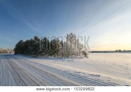 Snowy and icy, empty countryside winter road at sunset