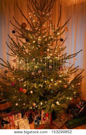 Christmas tree with beautiful decorations, fairy lights and presents underneath