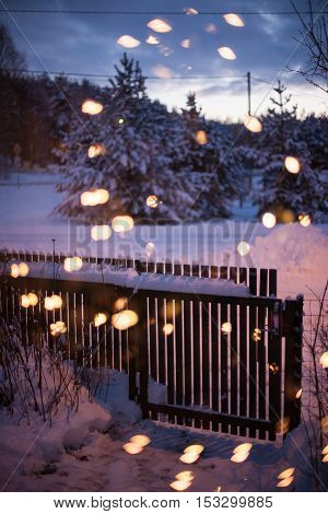 Wooden garden gate on a cold and snowy winter night with bokeh Christmas lights on the foreground