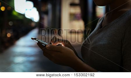 close up woman use phone on night in city