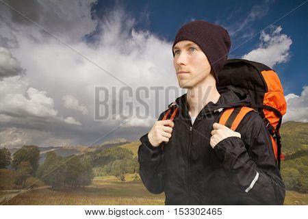 Hiker with backpack walking along a mountain terrain.