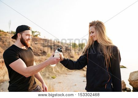 Healthy man and woman resting after training and drinking water while standing at the beah