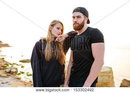 Young sports couple having a break from exercises outdoors at the seaside
