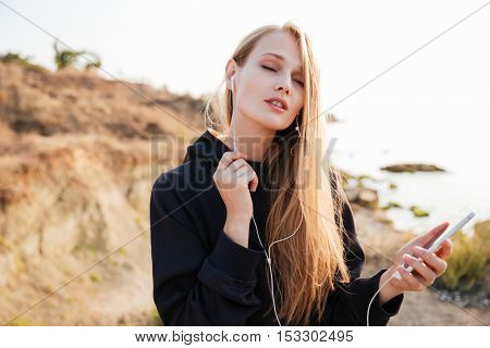 Portrait of a young fitness woman with eyes closed listening music with earphones and smartphone outdoors at the beach