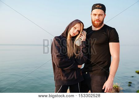Tired young sports couple with bottle of water standing together outdoors