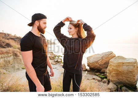 Young fitness man and woman resting after jogging standing at the beach