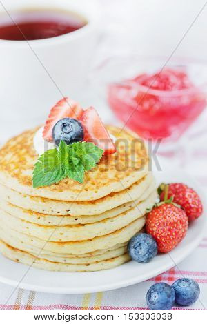 A stack of pancakes decorated with ripe raspberries blueberries and sour cream close-up