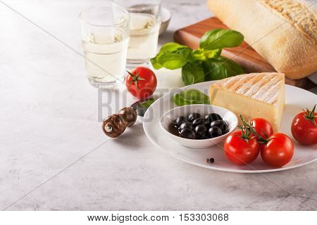 Italian appetizers view from above - bread ciabatta olives tomatoes cheese pepper fresh basil and wine ready for cooking with copy space