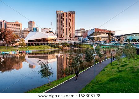 Adelaide Australia - September 11 2016: Torrens river bank with people walking through foot bridge in Adelaide city centre at sunset