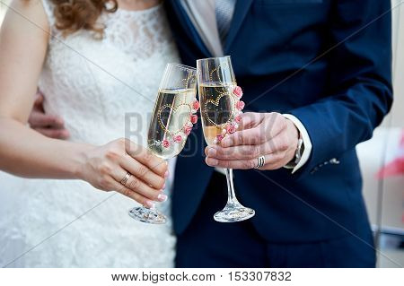 bride and groom are holding two glasses of champagne.