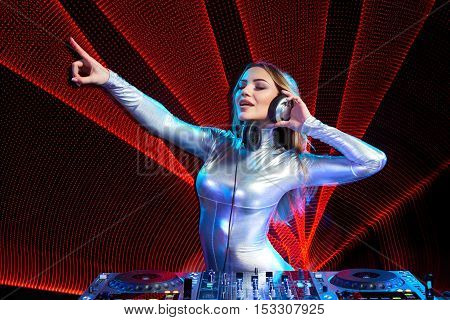 Beautiful DJ girl on decks at the party pointing to the side
