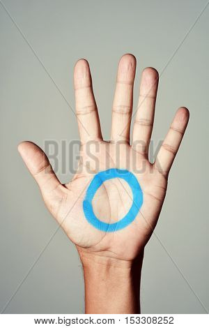 a blue circle, symbol of diabetes, painted in the palm of a young man, in support of diabetic people