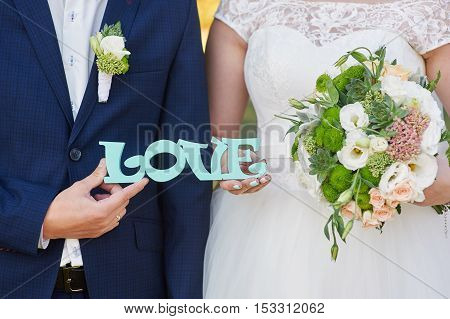 bride and groom holding bouquet and wooden word love.