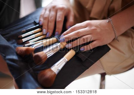 cosmetics bag with set of brushes for makeup and women's hands with a manicure