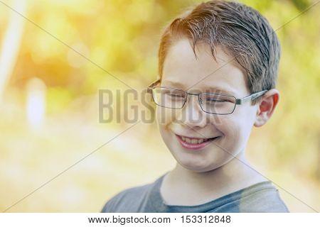 Happy boy wearing glasses in sunlight