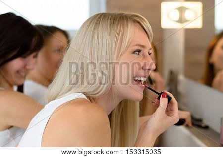 Smiling Attractive Blond Woman Applying Lip Gloss