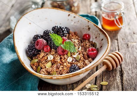 Homemade granola with blackberry and honey and milk rustic style. Healthy eating.Top view
