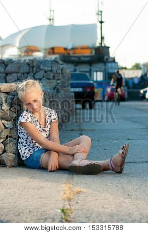 woman sits near a wall on the pavement in the background of cars
