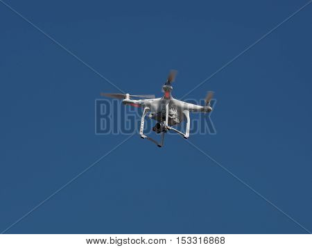Underneath bottom view of a drone with stabilizer camera flying aerial overhead against a blue sky