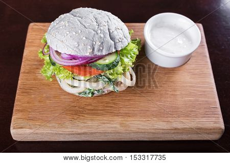 blue burger with fried squid and creamy spinach sauce on a wooden board