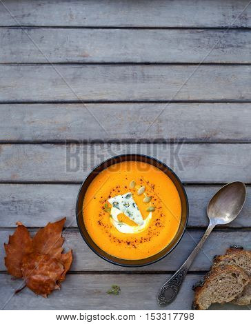 Hot pumpkin soup with blue cheese, herbs and multi-cereal bread on a wooden table with your text on top. View from above