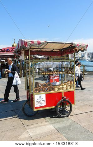 STANBUL TURKEY - MAY 20: Unidentified street vendor sells simits on a street on May 20 2016 Istanbul Turkey. Simit (Turkish) is a circular bread typically encrusted with sesame seeds.