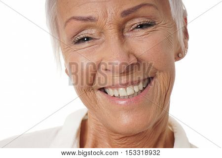 close-up headshot of older woman in her sixties with toothy smile