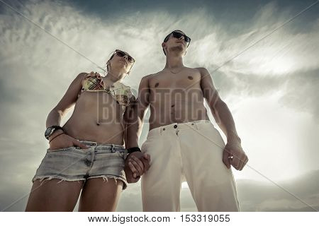 Couple stay on the beach under sky with sunlight.