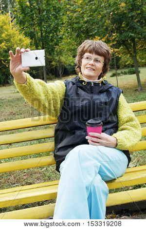 Attractive smiling elderly woman with cup of coffee, doing selfie with smart phone while sitting alone in public park. Old woman sitting in the park with cellphone and coffee.