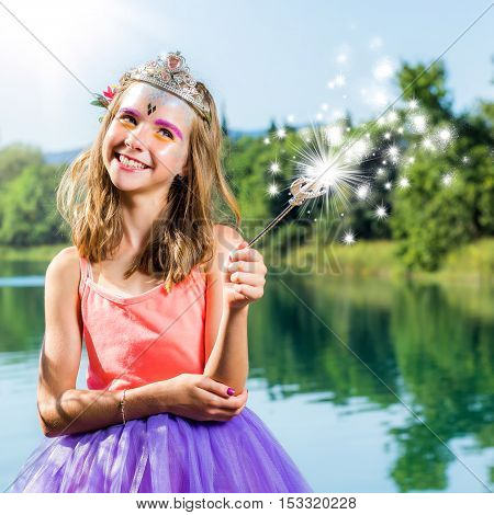 Close up portrait of little princess standing with magical wand next to lake. Girl casting magical charm with wand.