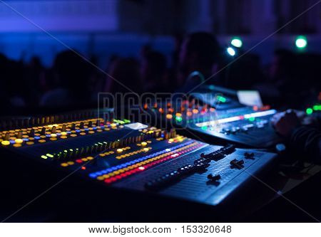 Soundman working on the mixing console in concert hall. Hands on the sliders.