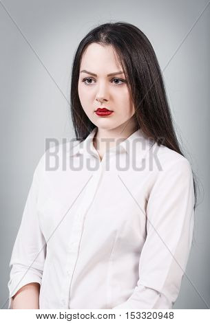 Young beautiful upset woman on the gray background