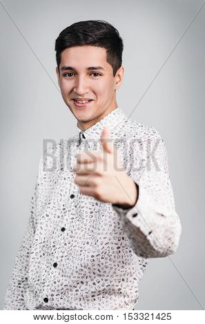Young handsome man showing OK sign on the gray background