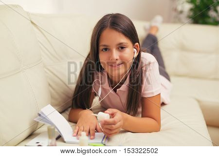 Little girl with headphones at home painted nails