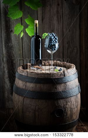 Red wine and grapes in glass on old barrel