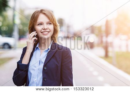 Young businesswoman speak on the phone and walking on the street