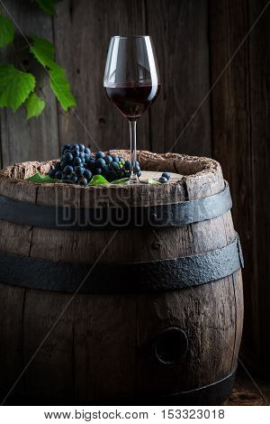 Glass Of Red Wine And Grapes On Old Wooden Barrel