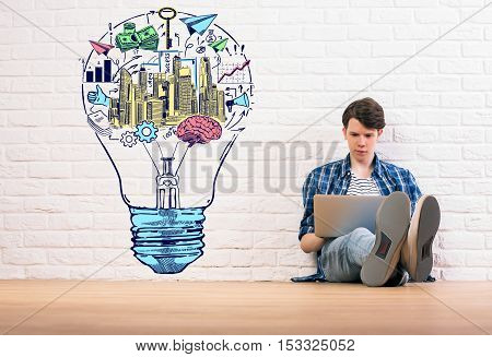 Young man sitting on wooden floor and using laptop on white brick wall background with creative colorful business sketch inside light bulb. Idea concept