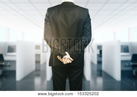 Businessman in suit with crossed hands behind back. Supervision concept