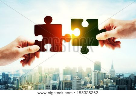 Hands putting puzzle piece together on bright city background with sunlight. Teamwork concept