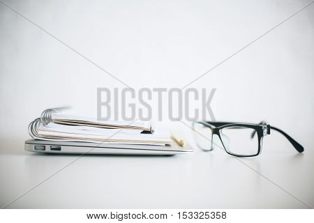 Close up of eyeglasses closed laptop and notepads on bright desktop