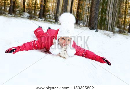 Cute little girl riding on snow slides in winter time
