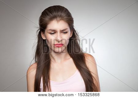 Upset woman feeling her guilty. With some contempt on her face. Studio portrait on grey vignette background.